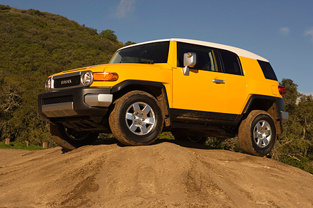 AUT 15 RK1017 01 © Kimball Stock 2007 Toyota FJ Cruiser Yellow And White Low 3/4 Side View On Top Of Dirt Hill