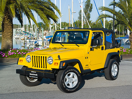 AUT 15 RK1045 01 © Kimball Stock 2006 Jeep Wrangler Yellow Front 3/4 View On Pavement By Harbor