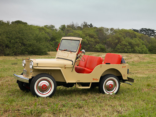 AUT 15 RK1118 01 © Kimball Stock 1962 Willys Jeep DJ 3A Tan 3/4 Side View On Grass