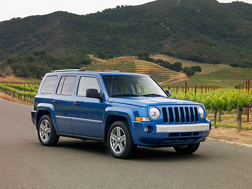 AUT 15 RK1126 01 © Kimball Stock 2007 Jeep Patriot Blue 3/4 Front View On Pavement By Vineyard