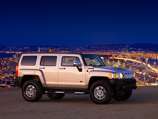 AUT 15 RK1160 01 © Kimball Stock 2007 Hummer H3 Silver 3/4 Front View On Pavement At Dusk City