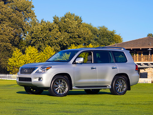 AUT 15 RK1165 01 © Kimball Stock 2008 Lexus LX 570 Silver 3/4 Front View On Grass By Building Trees Blue Sky