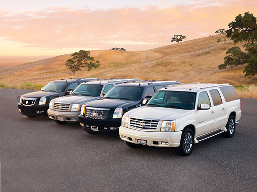 AUT 15 RK1208 01 © Kimball Stock 2007, 2004, 2007 & 2004 (L-R) Cadillac Escalades 3/4 Front View By Hills