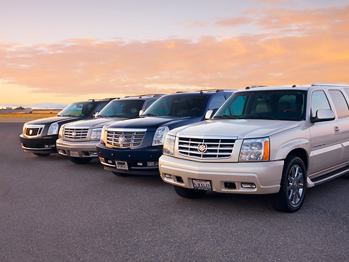 AUT 15 RK1210 01 © Kimball Stock 2007, 2004, 2007 & 2004 (L-R) Cadillac Escalades 3/4 Front View At Dusk