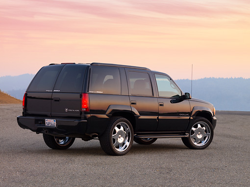 AUT 15 RK1211 01 © Kimball Stock 2000 Cadillac Escalade Black 3/4 Rear View On Pavement At Dusk