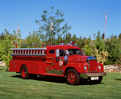 AUT 16 RK0051 03 © Kimball Stock 1959 Mack B85F Firetruck Red Front 3/4 View On Grass By Trees Blue Sky