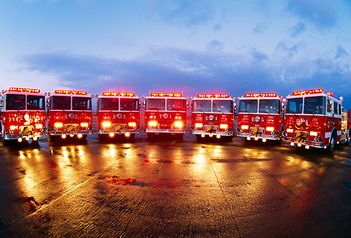 AUT 16 RK0086 16 © Kimball Stock Wide Angle Shot Of Fire Trucks Lined In A Row On Wet Pavement