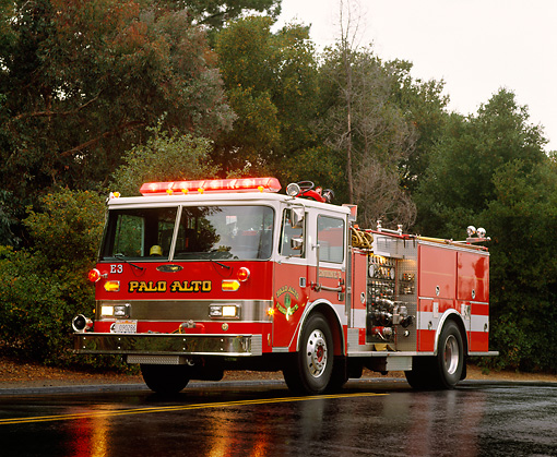 AUT 16 RK0095 02 © Kimball Stock 1988 Pierce 1500 GPM Pumper Front 3/4 View On Wet Road By Trees