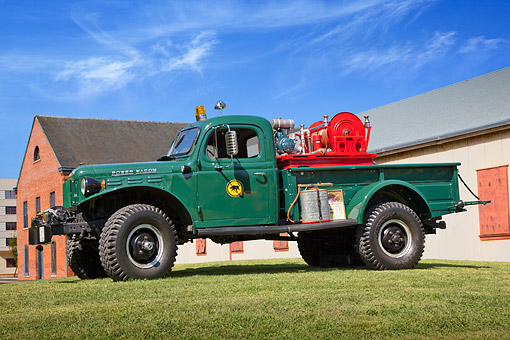 AUT 16 RK0192 01 © Kimball Stock 1962 Dodge Power Wagon Fire Truck Green Profile View On Grass By Brick Building