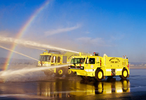 AUT 16 RK0028 29 © Kimball Stock 1997 Oshkosh T-1000 #8 And 1998 Teledyne P-23 #9 Crash Truck Yellow 3/4 Front View Spraying Water