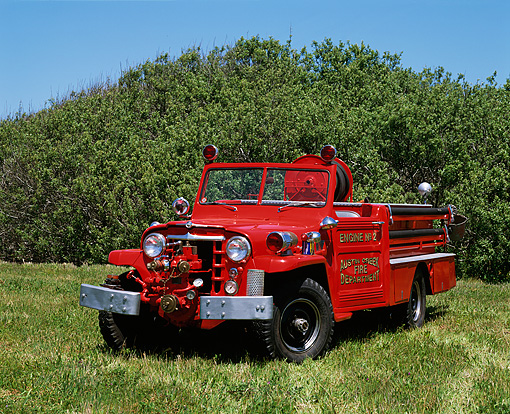 AUT 16 RK0039 02 © Kimball Stock 1953 Willys Fire Truck 3/4 Front View On Grass Blue Sky