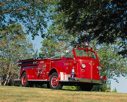 AUT 16 RK0040 09 © Kimball Stock 1954 American LaFrance 700 Series Firetruck 3/4 Side View On Grass By Trees