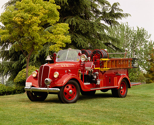 AUT 16 RK0050 04 © Kimball Stock 1937 Ford Van Pelt Firetruck Red 3/4 Front View On Grass By Trees