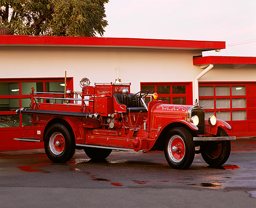 AUT 16 RK0100 07 © Kimball Stock 1921 Stutz Fire Truck 3/4 Front View On Wet Pavement By Building