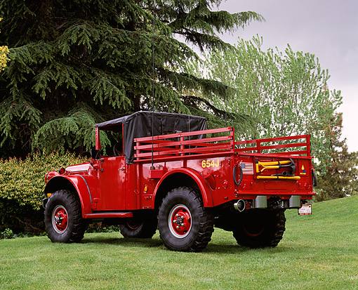 AUT 16 RK0112 02 © Kimball Stock 1952 Dodge M-37 Firetruck With CDF Red 3/4 Rear View On Grass By Trees