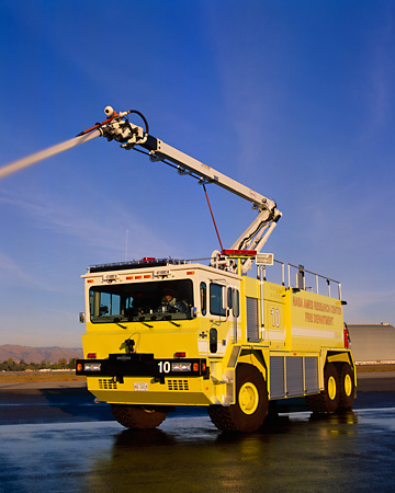 AUT 16 RK0123 12 © Kimball Stock 2002 Oshkosh TI 3000 ARFF Vehicle 3/4 Front View On Pavement Spraying Water