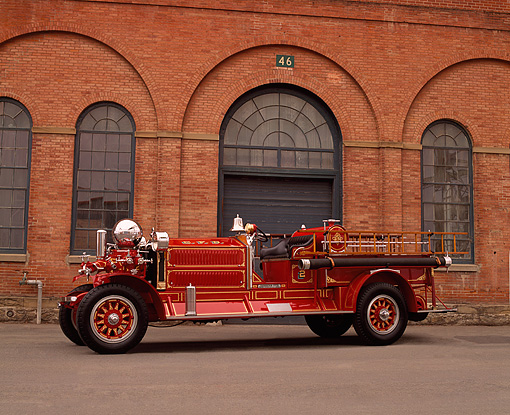 AUT 16 RK0129 01 © Kimball Stock 1923 Ahrens Fox Fire Engine Red 3/4 Side View On Pavement By Brick Building