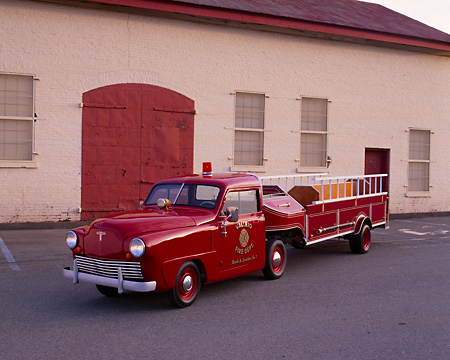 AUT 16 RK0132 01 © Kimball Stock 1949 Crosley Ladder Firetruck Red 3/4 Front View By Garage