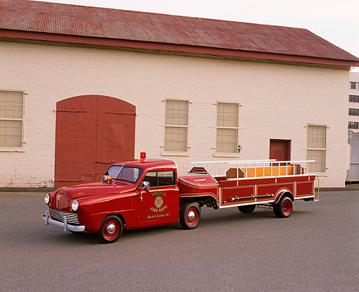 AUT 16 RK0133 02 © Kimball Stock 1949 Crosley Ladder Fire Truck Red 3/4 Front View On Pavement By Building