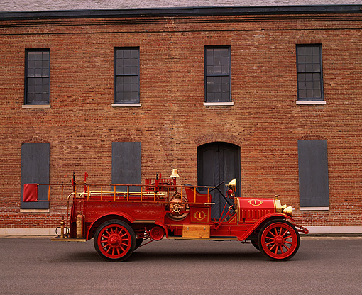 AUT 16 RK0136 04 © Kimball Stock 1909 Kissel Hose And Chemical Firetruck Red Profile View On Pavement By Brick Building