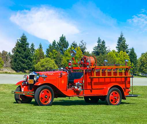 AUT 16 RK0146 01 © Kimball Stock 1930 Ford Model A Fire Truck Red 3/4 Front View By Trees Blue Sky