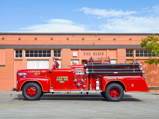 AUT 16 RK0157 01 © Kimball Stock 1954 Ahrens-Fox Fire Truck Red Profile View By Building