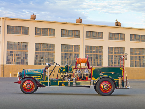 AUT 16 RK0163 01 © Kimball Stock 1916 Locomobile Fire Truck Green Profile View By Building