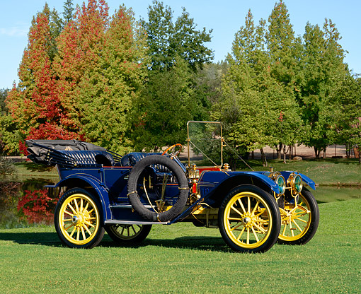 AUT 17 RK0049 03 © Kimball Stock 1910 Oldsmobile LTD Touring Car 3/4 Front View on Grass By Stone Wall Blue Sky