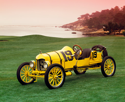 AUT 17 RK0101 02 © Kimball Stock 1919 Ford Model T Speedster Yellow And Black 3/4 Front View On Grass By Water Red Sky Pebble Beach