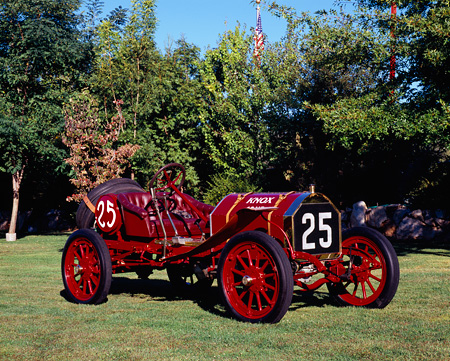 AUT 17 RK0151 04 © Kimball Stock 1910 Knox Race Car Red 3/4 Side View On Grass By Trees