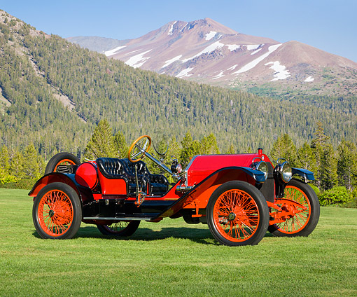 AUT 17 RK0203 01 © Kimball Stock 1913 Stutz Bearcat Red 3/4 Side View On Grass By Mountains And Trees