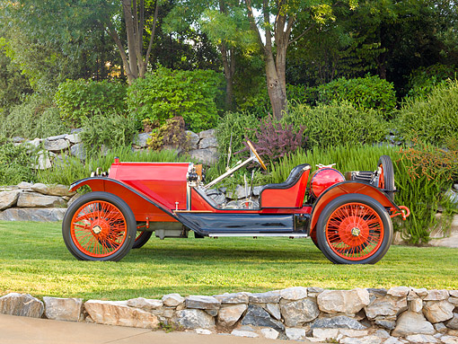 AUT 17 RK0206 01 © Kimball Stock 1913 Stutz Bearcat Red Profile View On Grass By Stone Wall And Trees