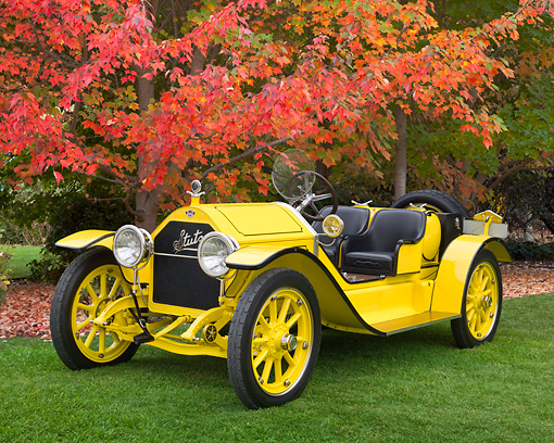 AUT 17 RK0207 01 © Kimball Stock 1915 Stutz Bearcat Yellow 3/4 Front View On Grass By Autumn Trees