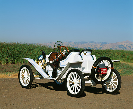 AUT 17 RK0024 01 © Kimball Stock 1914 Ford Model T Speedster White 3/4 Rear View On Pavement Green Fields