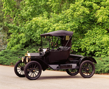 AUT 17 RK0041 01 © Kimball Stock 1915 Ford Model T Roadster Black 3/4 Front View On Pavement By Trees