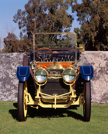 AUT 17 RK0051 03 © Kimball Stock 1910 Oldsmobile LTD Touring Car Head On Shot On Grass By Stone Wall