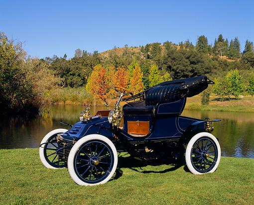 AUT 17 RK0065 01 © Kimball Stock 1906 Autocar Type X Roadster Side 3/4 View On Grass By Water Fall Trees