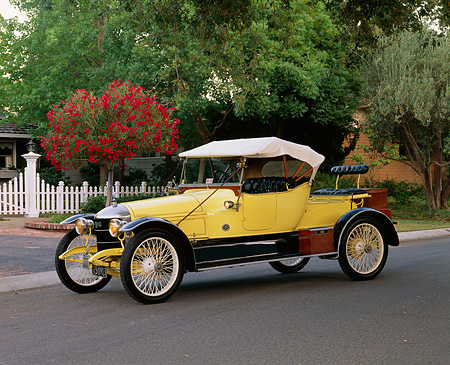 AUT 17 RK0091 04 © Kimball Stock 1913 Star Gentleman's Roadster Yellow 3/4 Front View By House Trees Fence