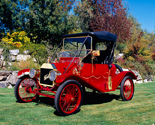 AUT 17 RK0137 01 © Kimball Stock 1911 Ford Model T Torpedo Red And Black 3/4 Side View On Grass By Trees And Bushes