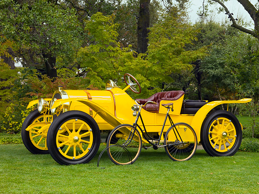 AUT 17 RK0172 01 © Kimball Stock 1913 Pope Hartford Portola Roadster Yellow Front 3/4 View On Grass With 1901 Cleveland Chainless Bicycle Black