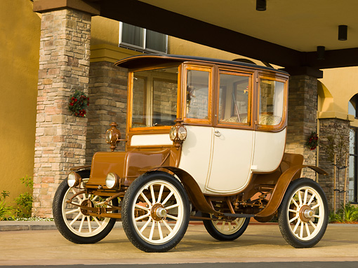 AUT 17 RK0184 01 © Kimball Stock 1909 Rauch & Lang Electric Brougham Brown And Cream 3/4 Front View On Pavement By Building