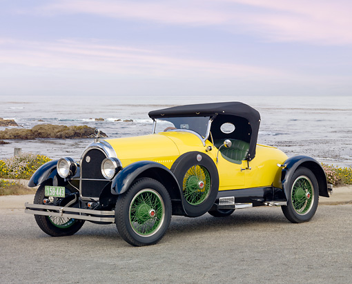 AUT 18 BK0001 01 © Kimball Stock 1924 Kissel 6-55 Speedster Yellow 3/4 Front View On Pavement By Beach