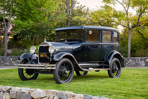AUT 18 BK0012 01 © Kimball Stock 1929 Ford Model A Fordor Sedan Black 3/4 Front View By Trees