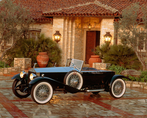 AUT 18 RK0018 05 © Kimball Stock 1924 Rolls Royce Silver Ghost Boattail Speedster Black 3/4 Side View On Driveway By House