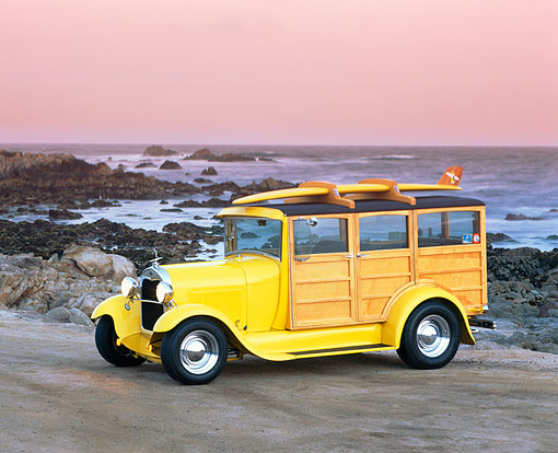 AUT 18 RK0035 04 © Kimball Stock 1929 Ford Woody Yellow With Surfboard 3/4 Side View On Sand By Ocean