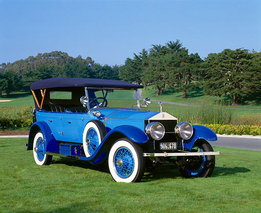 AUT 18 RK0061 02 © Kimball Stock 1923 Rolls Royce Silver Ghost Blue 3/4 Front View On Grass Trees Blue Sky