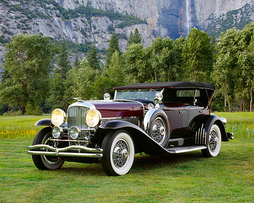 AUT 18 RK0067 02 © Kimball Stock 1929 Duesenberg Phaeton Dual Cowl Black 3/4 Front View On Grass By Mountain