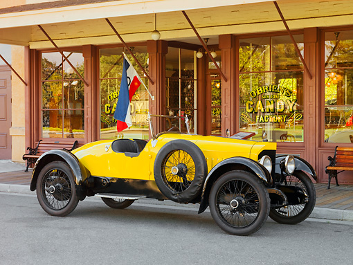 AUT 18 RK0749 01 © Kimball Stock 1920 Biddle Speedway Special Yellow 3/4 Front View On Pavement By Building