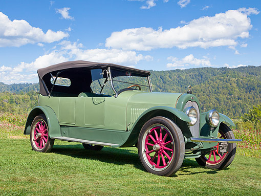 AUT 18 RK0808 01 © Kimball Stock 1920 Overland Roadster Green 3/4 Front View On Grass By Mountains And Trees