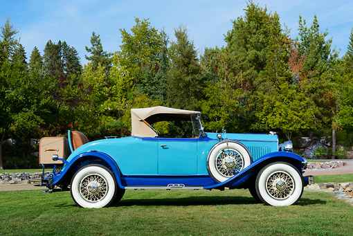 AUT 18 RK0831 01 © Kimball Stock 1929 Chrysler 75 Roadster Blue Profile View On Grass By Trees